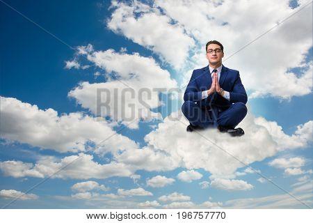 Businessman meditating in the sky