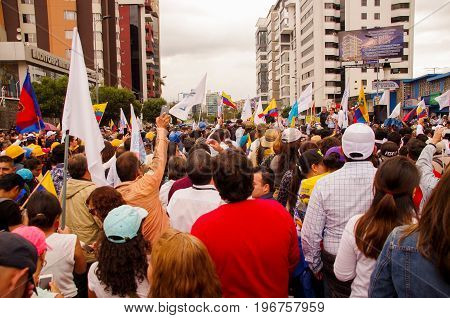 Quito, Ecuador - April 7, 2016: Crowd of unidentified people with ecuadorian and white flags supporting the presidential candidate Guillermo Lasso, and journalists during anti government protests in Shyris Avenue.