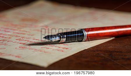 Handwritten Letter And An Ink Pen On A Wooden Desk
