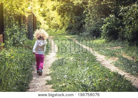 Carefree happy childhood with playful child walking alone on rural footpath in forest during summer holidays
