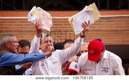 Quito, Ecuador - April 7, 2016: Closeup opposition leader Andres Paez surrounded by people and holding in his hands proofs of election fraud, police and journalists during anti government protests in Shyris Avenue.