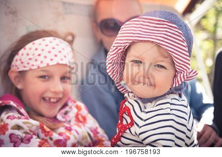 Funny cheerful baby with family outdoors symbolizing happiness