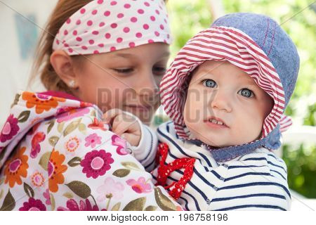 Funny cheerful baby outdoors with embracing her sister symbolizing togetherness and happiness