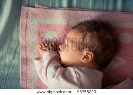 Sleeping newborn baby on soft blanket with daylight