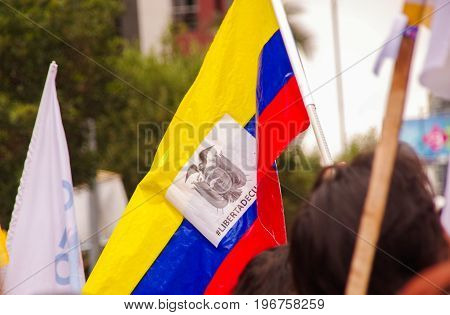 Quito, Ecuador - April 7, 2016: Closeup of an Ecuadorian flag holded by a person, claiming for liberty and supporting the presidential candidate Guillermo Lasso, and journalists during anti government protests in Shyris Avenue.