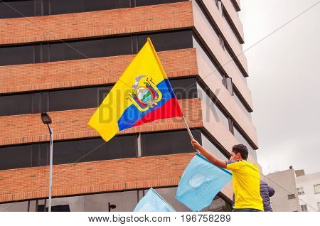 Quito, Ecuador - April 7, 2016: Unidentified man with ecuadorian flag supporting the presidential candidate Guillermo Lasso, and journalists during anti government protests in Shyris Avenue.
