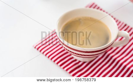 Red coffee cup over kitchen towel. View from above. Isolated on white background
