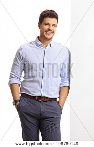 Elegant guy leaning against a wall and smiling isolated on white background