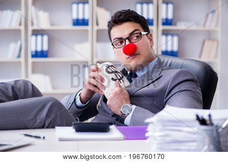 Clown businessman in the office with the a money sack