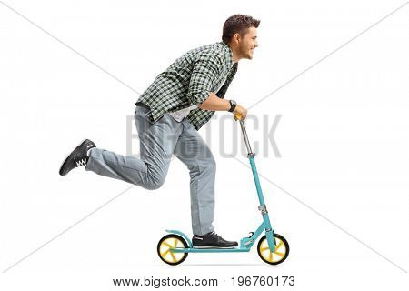 Profile shot of a young man riding a scooter isolated on white background
