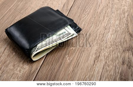 Old used men's purse with money on wood background
