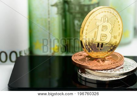 Golden Bitcoin on smartphone over Euro banknotes money background