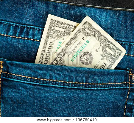 Blue trendy jeans with two american dollars bill on its pocket
