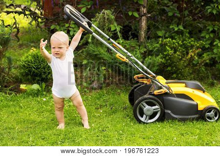 Cute Toddler With A Lawnmower Cutting Grass
