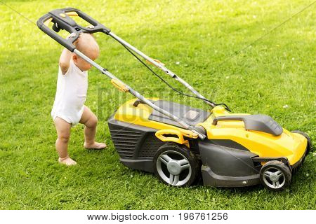 Funny baby boy cuts the lawn with a grassmower.