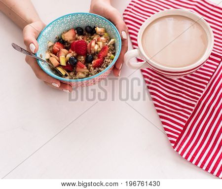 Healthy breakfast - cup of coffee, muesli and fresh berries on white wooden background, top view, health concept