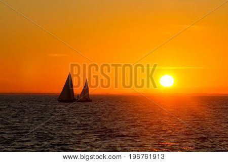 Two sailboats sailing in the summer sunset