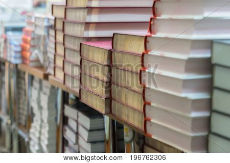 Abstract blurred background of pile of books, textbooks or fiction in book store or in library. Education, school, study, reading fiction concept.