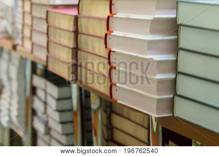 Close-up of stops of books, textbooks or fiction in book store or in library. Education, school, study, reading fiction concept. Abstract blurred background