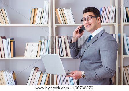 Businessman with a laptop talking on phone working in library