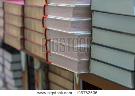 Many books, textbooks or fiction in rows lying on the shelves in library or in the modern urban bookshop. Self-study, educational, manuals, textbooks, school, study concept. Blurred abstract background