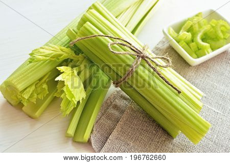 bunch of stalks of fresh green celery on flax material background tied up by flax rope healthy diet concept