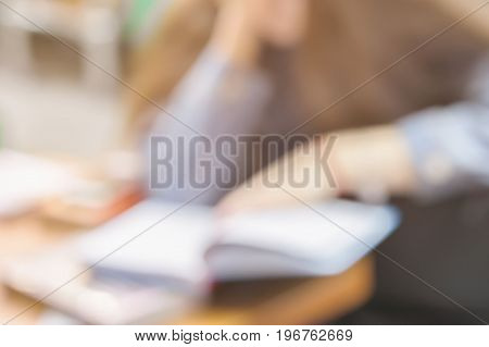 Close-up of Book in the hands of a young girl in book store or in library, which attentively reading a book, abstract blurred image. Concept of education, manuals, textbooks, school, study
