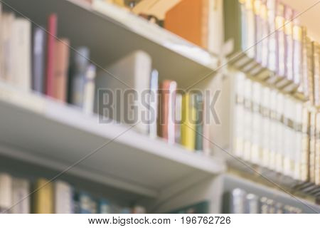 Blurred background of different colorful books lying on bookshelfs in the urban bookshop, vintage picture