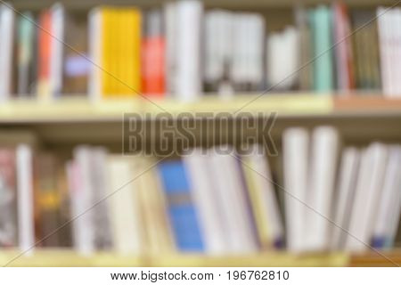 Blurred school library bookshelf with colorful book, smanuals and textbooks. Education, school, study concept. For abstract background