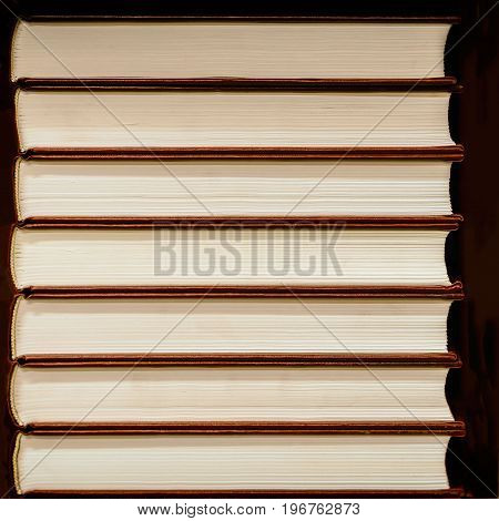 Heap of closed books in hard covers on a dark background