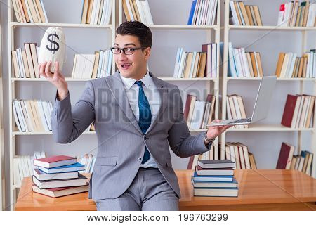 Businessman in library with a money sack and a laptop
