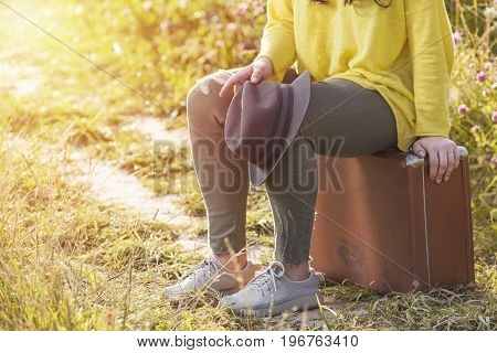 Tired girl sitting and resting on brown vintage suitcase in the field road during summer sunset. Toned image and travel concept