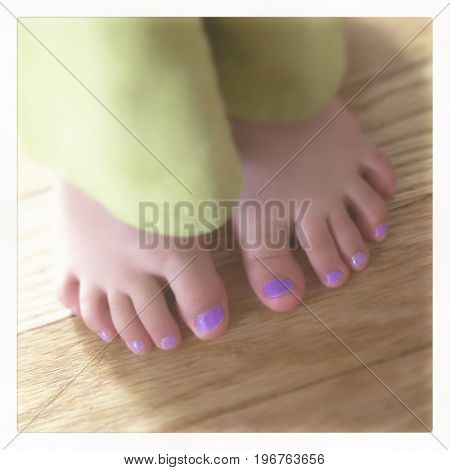 Little toddler girl's toes painted with nail polish