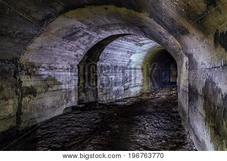 Abandoned military bunker tunnel with concrete walls
