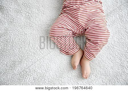 Cute little baby lying on plaid at home