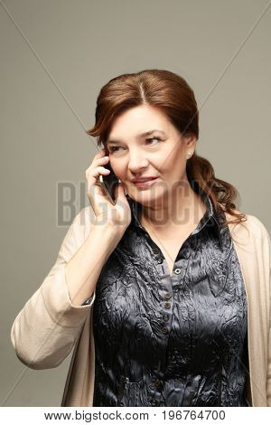 Beautiful elderly woman posing with phone on light background