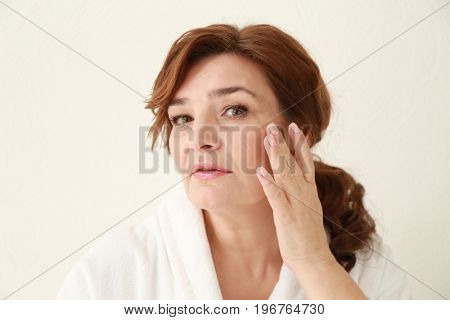 Beautiful elderly woman posing on light background