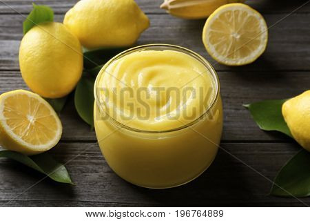 Beautiful composition with delicious lemon curd on wooden table
