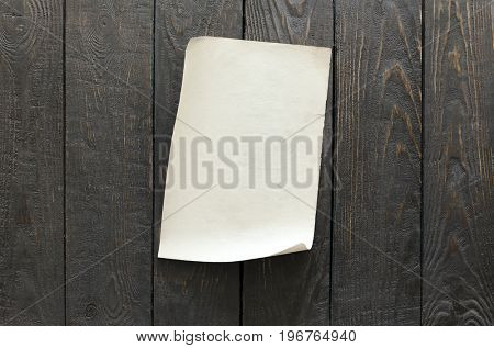 old paper on dark brown wooden wall, retro background