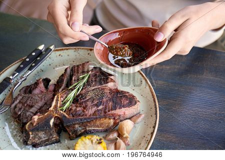 Woman adding mustard sauce to medium rare beefsteak