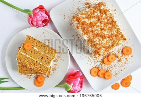 sweet carrot cake dessert slices with cream from sour cream white wooden background spring pink tulip flowers top view