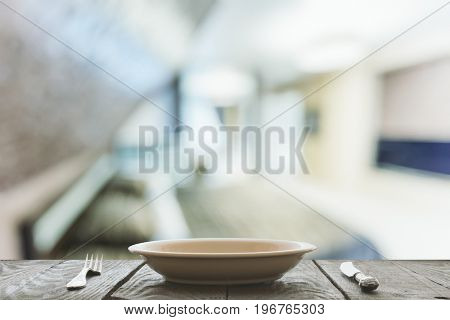 empty plate with fork and knife on wooden table in the bedroom