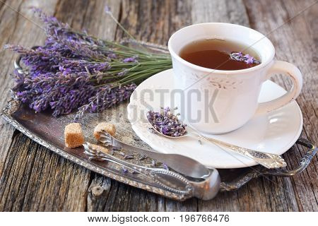 Summer mood: Аromatic lavender tea and fresh lavender on vintage tray rustic style on old wooden background