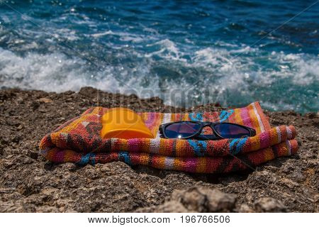 Sunscreen, Colorful Towel And Sunglasses On The Rocky Beach With Sea Waves In The Background