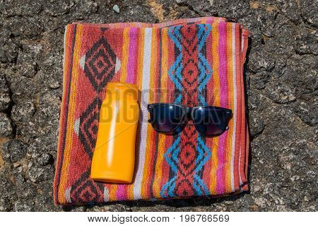 Sunscreen, Colorful Towel And Sunglasses On The Rocky Beach