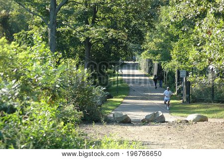 Manville Rhode Island USA - September 10 2006: People enjoying shaded stretch of Blackstone River Bikeway