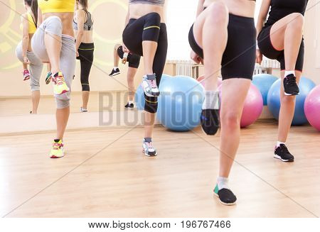 Sport Concepts. Closeup of Legas of Four Caucasian Female Athletes Having Body Stretching Exercises in Sport Gym.Horizontal Image Composition