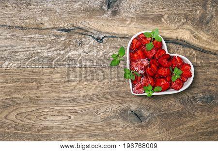 Strawberries heart on rustic wooden background. Food. Fruits. Berries