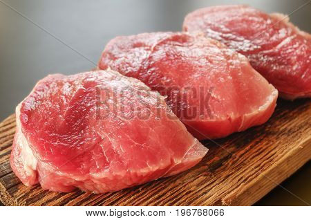 Raw pork meat lices on cutting board. Close up steak