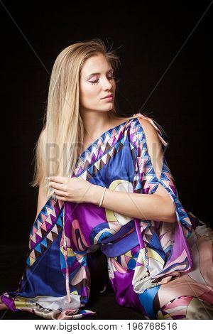 beauty young blonde woman portrait with interesting  makeup eyelashes and crystals in colorful silky dress studio shot